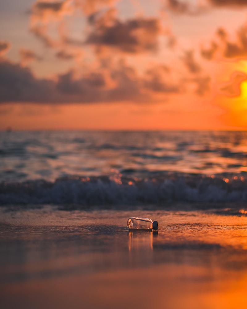 bottiglia di plastica in spiaggia - viaggiare in modo sostenibile